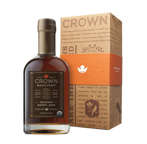 """Make an uncommon impression with the distinctive Crown Maple Bourbon Barrel Aged 375ML (12.7 FL OZ) organic maple syrup bottle in an elegant Royal Treatment box with your choice of our signature classic orange band or HAPPY HOLIDAYS band.  Distinctive aromas and flavors of bourbon, smoky oak, graham cracker, brown butter & creamy vanilla are showcased in Crown Maple Bourbon Barrel Aged organic maple syrup which presents exceptional layers of luxurious flavors.  First, certified organic, pure maple syrup is aged in barrels to absorb the flavor of bourbon from the oak. Then, we bottled it at our state-of-the-art sugarhouse in Dover Plains, in New York's Hudson Valley. The elegant packaging of this unique syrup is designed to reflect the superb quality of the product within, described in The Wall Street Journal as """"soul-stirring""""."""