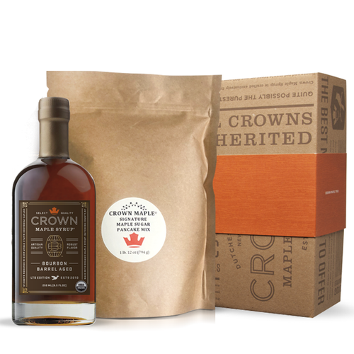 """Gather around the breakfast table and indulge with estate-produced, organic Crown Maple syrup and our signature pancakes. Fresh from the Crown Maple Estate, our artisan quality recipe delivers a distinctive pancake experience featuring Crown Maple sugar and Crown Maple sugar pearls that explode with maple flavor on the griddle.  The Pancake Breakfast pack includes one Crown Maple Pancake Mix 28 Oz. (794g) and your choice of Crown Maple syrup 375 ML (12.7 FL OZ)—Amber Color Rich Taste, Dark Color Robust Taste, or 250 ML (8.5 FL OZ) flavor infused artisan syrup—Bourbon Barrel Aged, Madagascar Vanilla Infused, Cinnamon Infused organic maple syrup.  Ships in our distinctive Royal Treatment box with your choice of our signature ORANGE band or HAPPY HOLIDAYS RED band.  Contains:  Wheat  This product is produced and packed in a facility and on equipment that processes milk, egg, fish, crustacean shellfish, tree nuts, wheat, peanuts, and soy.  BOURBON BARREL AGED  Described by The Wall Street Journal as """"soul-stirring"""", the Crown Maple Bourbon Barrel Aged organic maple syrup is estate-produced in NY's Hudson Valley and showcases distinctive aromas and flavors of maple, bourbon, smoky oak, graham cracker, brown butter & creamy vanilla with exceptional layers of luxurious flavors.   We take estate-produced maple syrup and age it in barrels to absorb the bourbon from the oak. The barrel features super-premium, 10-year bourbon from Widow Jane, based in Brooklyn NY. This aging process may leave trace amounts of alcohol in the bourbon barrel aged maple syrup. You will find yourself adding this to everything from yogurt to oatmeal, as a sweetener for coffee, as a versatile ingredient for bourbon maple glazed salmon, meats and vegetables, in a vinaigrette, in place of simple syrup for cocktail mixology, and of course to create an exceptional breakfast of pancakes, waffles, French toast, and bacon!"""