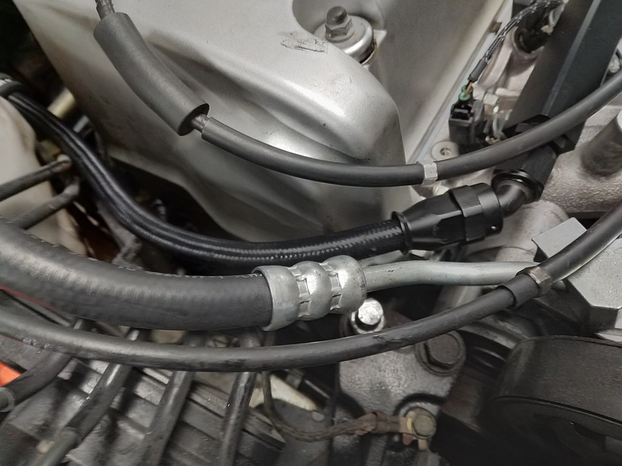 Feed Line as It connects to the fuel rail. Requires the Power steering hose to be bent out of the way and motor mount bolt to be cut or swapped with a bolt.
