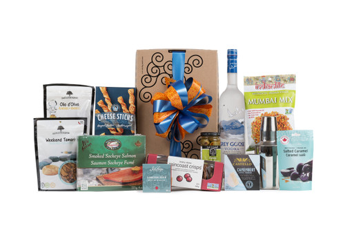 Gourmet gift box featuring Grey Goose vodka, a martini shaker, and snacks (crackers, cheese, pate, etc.).