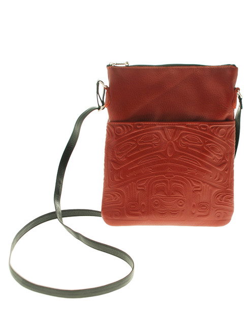 Red leather over-the-shoulder bag, embossed with West Coast First Nations bear design.