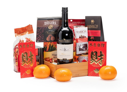 Gourmet gift basket featuring Mission Hill cabernet sauvignon, sweet and savoury snacks (chocolate, crackers, nuts, etc.), mandarins, and lucky red envelopes, presented on a bamboo tray.