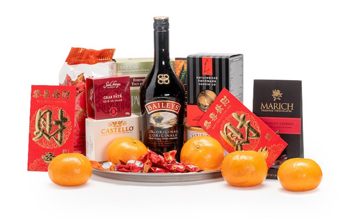 Gourmet gift basket featuring Bailey's Irish cream, sweet and savoury snacks (chocolate, crackers, nuts, etc.), mandarins, and lucky red envelopes, presented on a silver tray.