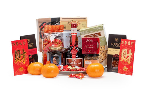 Gourmet gift basket featuring Grand Marnier, sweet and savoury snacks (chocolate, crackers, nuts, etc.), mandarins, and lucky red envelopes, presented on a silver tray.