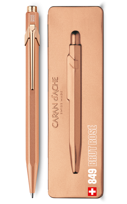 Rose gold pen beside pen case.