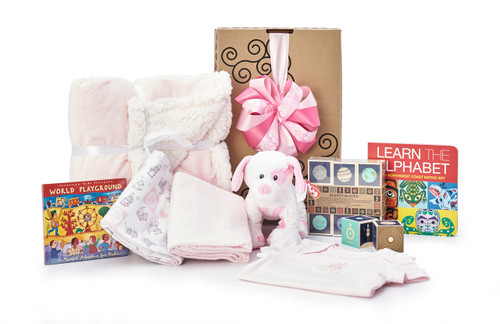 Gift basket for new baby, featuring pink blanket, pink clothing, and toys.