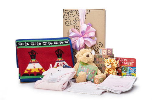 Gift basket for new baby, featuring Pendleton blanket, pink clothing, teddy bear and other toys.