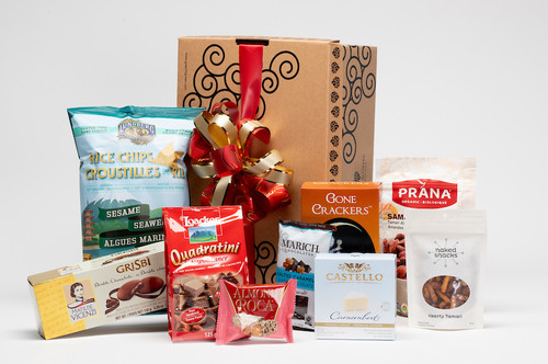 Gourmet gift basket featuring sweet and savoury snacks (chocolate, chips, crackers, etc.) packaged in signature Green & Green gift box with red and gold ribbon and bow.