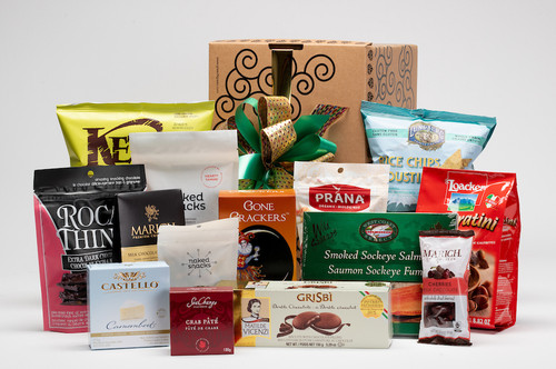 Gourmet gift basket featuring sweet and savoury snacks (chocolate, chips, crackers, pate, etc.) packaged in signature Green & Green gift box with green and gold ribbon and bow.