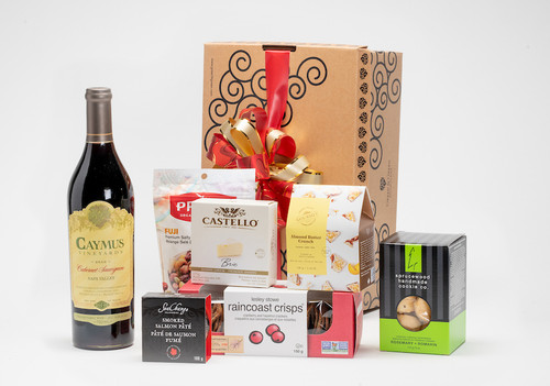 Gourmet gift basket featuring Caymus Vineyards cabernet sauvignon, and BC local snacks (crackers, cheese, chocolate etc.) packaged in signature Green & Green gift box with red and gold ribbon and bow.