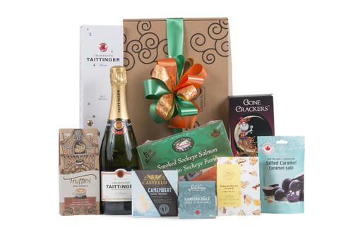 Gourmet gift basket featuring Taittinger Brut Réserve Champagne paired with sweet and savoury snacks (chocolate, crackers, nuts, etc.), packaged in signature Green & Green gift box with ribbon and bow.