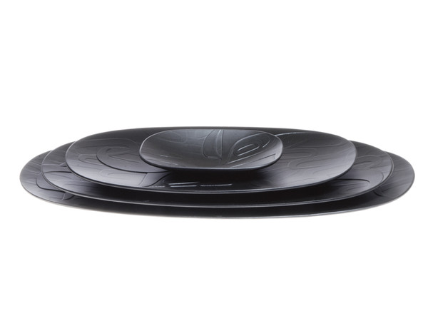 Four black oval nesting platters, etched with a West Coast First Nations abstract design.