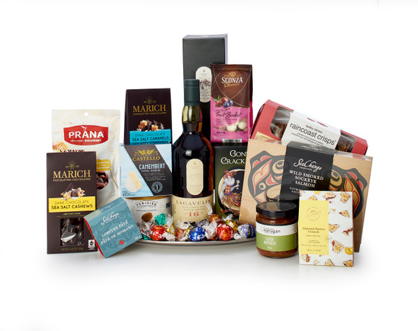 Gourmet gift basket featuring Lagavulin single malt scotch, sweet and savoury snacks (chocolate, crackers, nuts, etc.), presented on a silver tray.