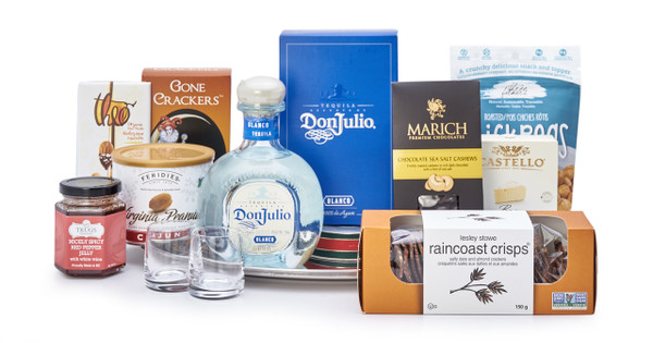 Gourmet gift basket featuring Don Julio tequila blanco, sweet and savoury snacks (chocolate, crackers, nuts, etc.), and Riedel shot glasses, presented on a silver tray.