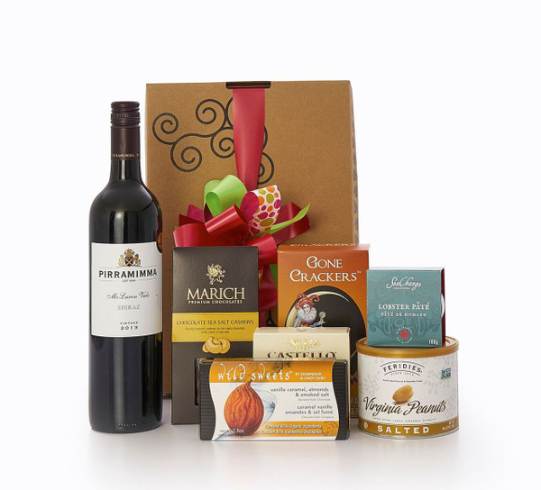 Gourmet gift basket featuring Pirramimma shiraz, and sweet and savoury snacks (chocolate, crackers, nuts, etc.), packaged in signature Green & Green gift box with red and green ribbon and bow.