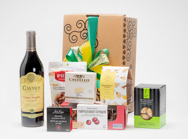 Gourmet gift basket featuring Caymus Vineyards cabernet sauvignon, and BC local snacks (crackers, cheese, chocolate etc.) packaged in signature Green & Green gift box with green and yellow ribbon and bow.