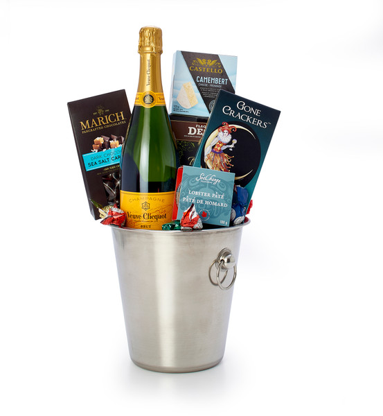 Gourmet gift basket featuring Veuve Clicquot Yellow Label Brut , and sweet and savoury snacks (chocolate, crackers, cheese, etc.), presented in a champagne bucket.