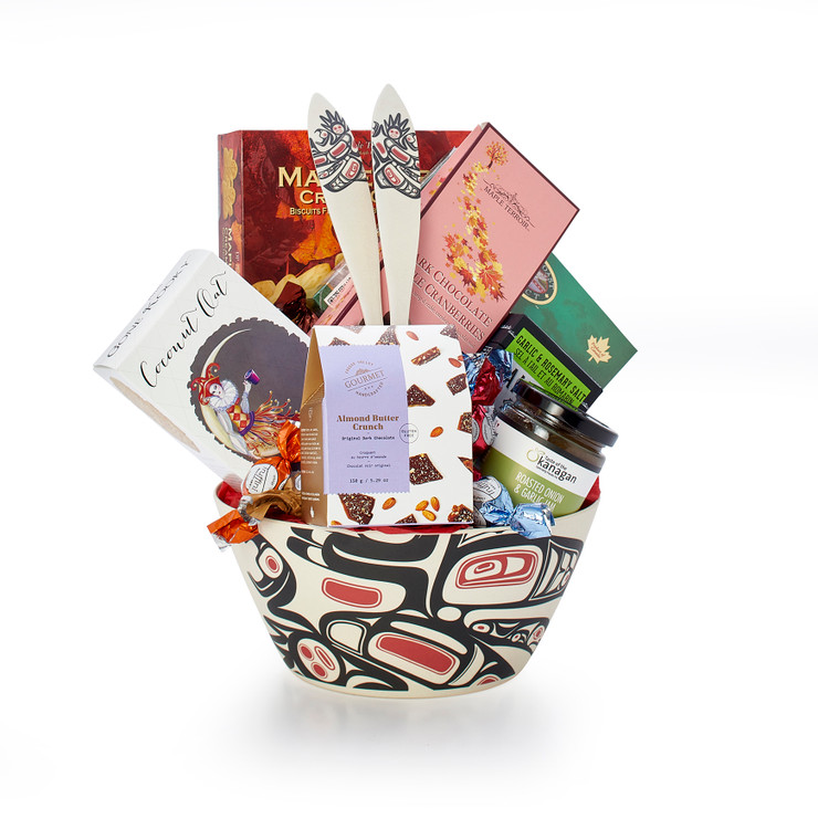 Gourmet gift basket featuring BC local snacks (chocolate, crackers, smoked salmon, etc.) and salad servers with a First Nations design, packaged in a modern potlatch bowl featuring West Coast First Nations abstract design.