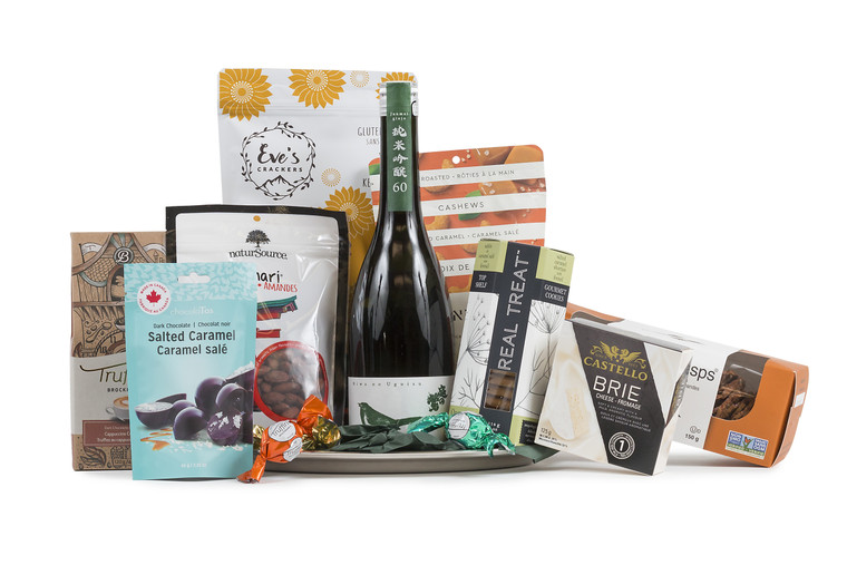 Gourmet gift basket featuring Niwa no Uguisu 60 Junmai Ginjo sake paired with sweet and savoury snacks (chocolate, crackers, nuts, etc.), packaged in signature Green & Green gift box with ribbon and bow.