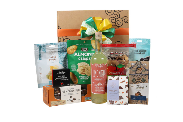 Gourmet gift basket featuring The Woods Limoncello paired with sweet and savoury snacks (chocolate, crackers, nuts, etc.), packaged in signature Green & Green gift box with ribbon and bow.