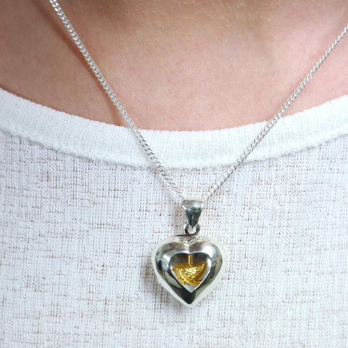 Lily Blanche sterling silver heart locket with gold bird inside modelled