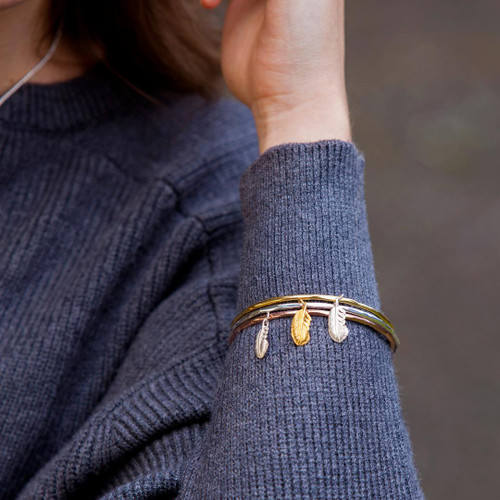 Lily Blanche Feather Bangle in Silver with gold feather charm, modelled