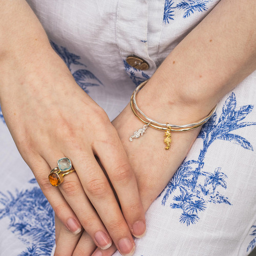 model wearing silver bangle with gold seahorse charm attached