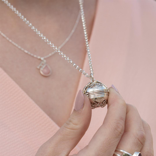 Image of the Lily Blanche White Gold 6 Photo Memory Keeper Locket worn by a model holding the locket