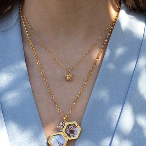 model wearing gold beaded chain with gold bee charm