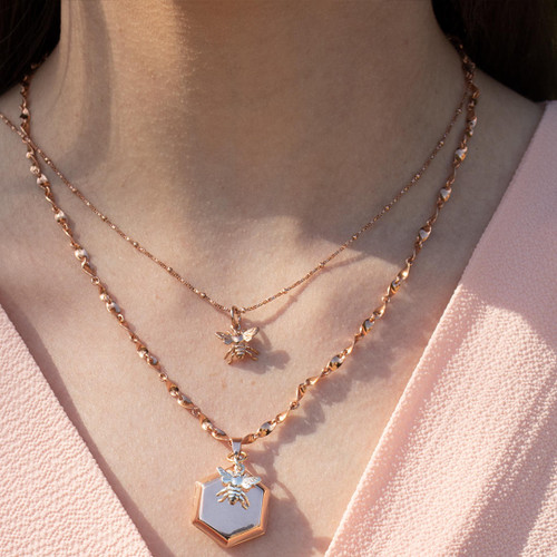 model wearing rose gold beaded chain with rose gold bee charm