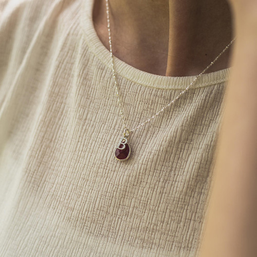 model wearing white gold beaded chain with silver birthstone and initial
