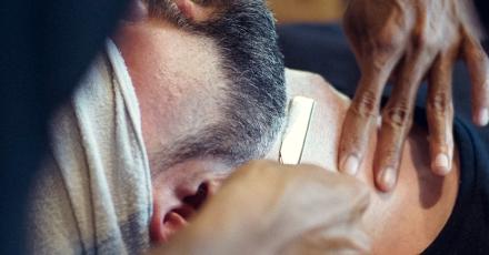 Barber shaving customer with straight razor