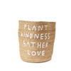 "tall standing jute basket with white embroidery that reads ""plant kindness gather love"""