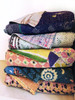 stack of 5 different kanthan quilts showing off the variations in colors and patterns