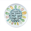 "white plate with colorful flower and the quote ""don't plant anything but love"""