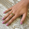 gold ring with green apatite stone on hand