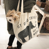 tote bag with a small fluffy dog hanging out the side