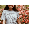 someone wearing the save the bees shirt in front of pink flowers
