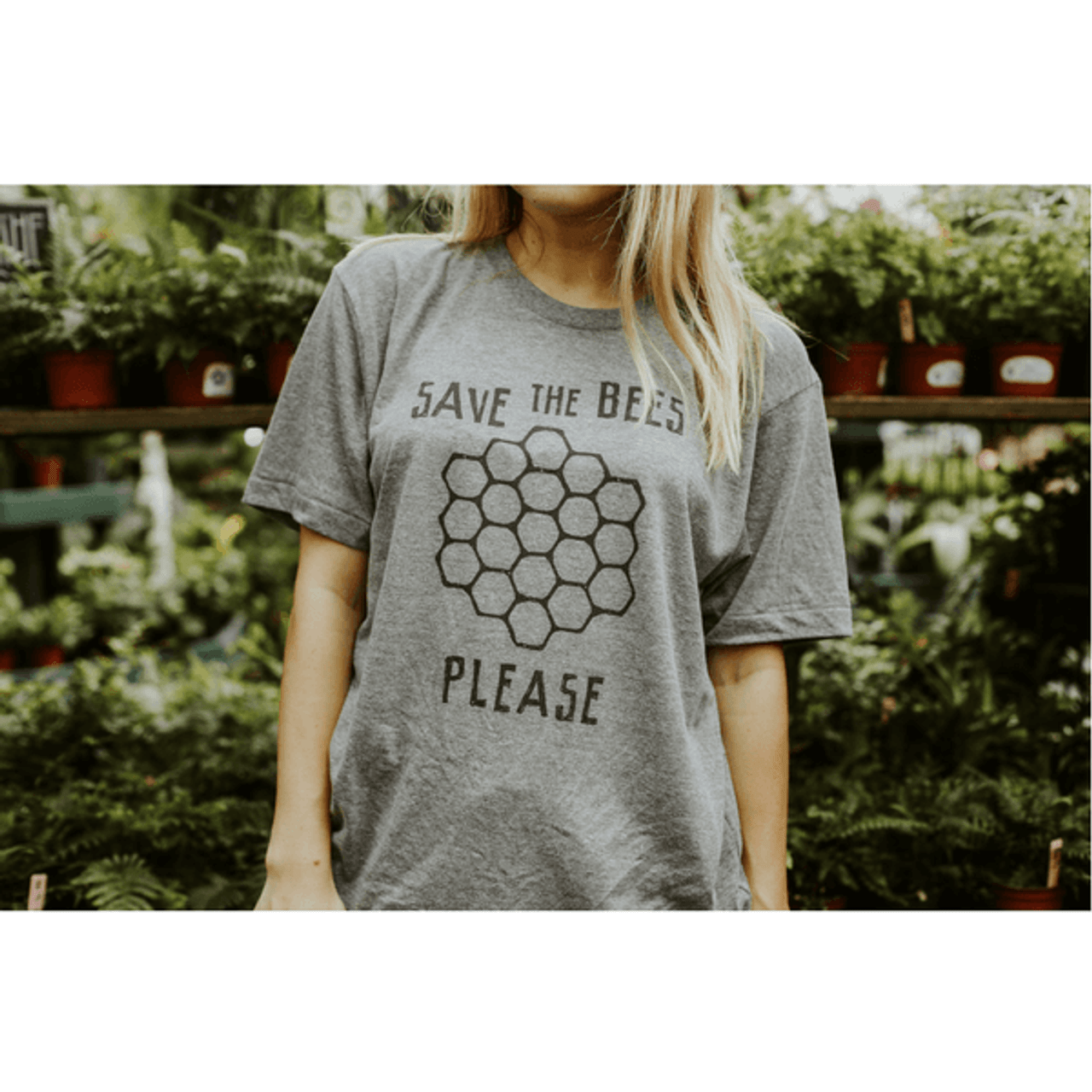 someone wearing the save the bees please shirt in front of potted plants