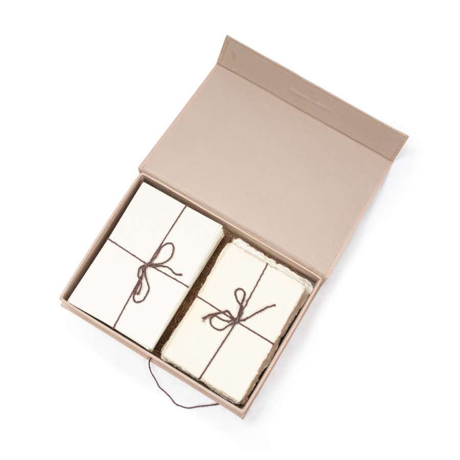 blush stationary box with with the deckle edged envelops on the left side and the deckle edged cards on the right wrapped in twine