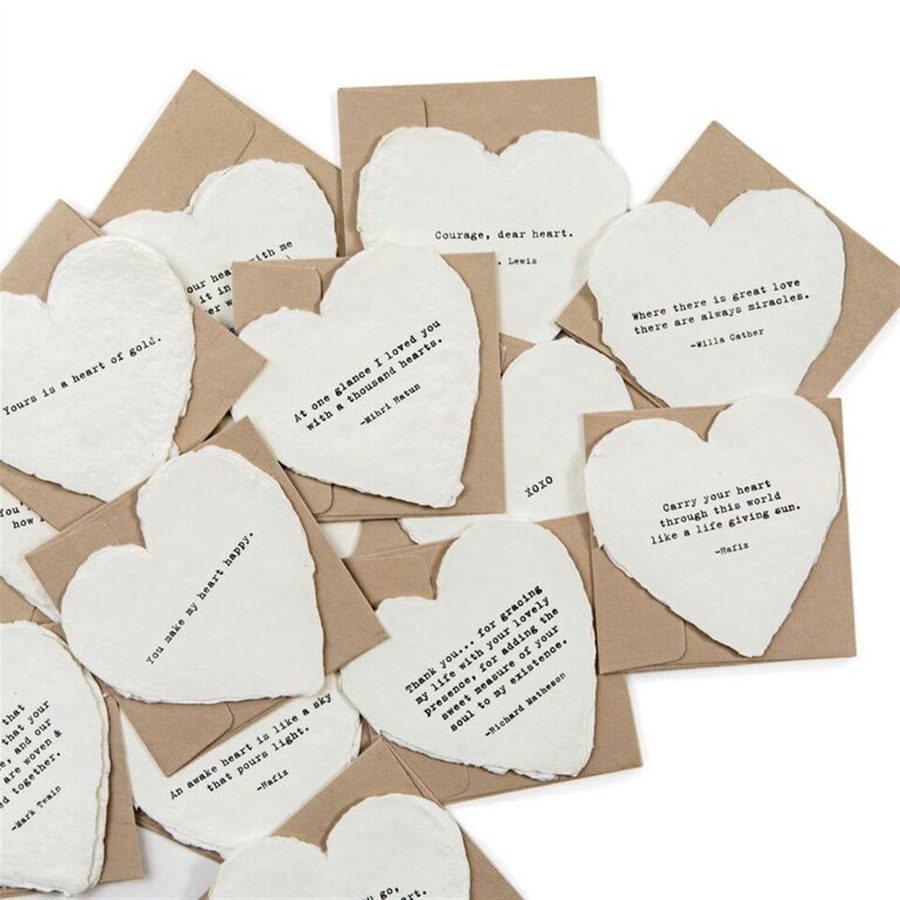 collection of different cream colored heart shaped cards with deckled edges and their brown craft envelopes