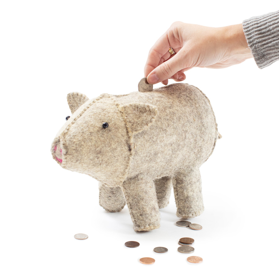 grey felt pig shaped piggy bank with hand putting coins in the slot on top of piggy bank