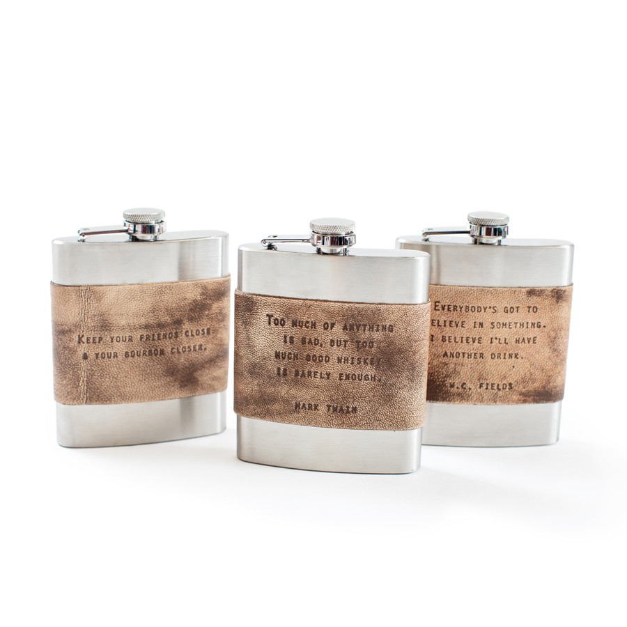 three metal flasks with a leather strip with a quote stamped in the leather