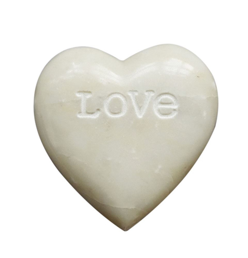 "an off white soapstone shaped heart with the word ""Love"" engraved on the face."