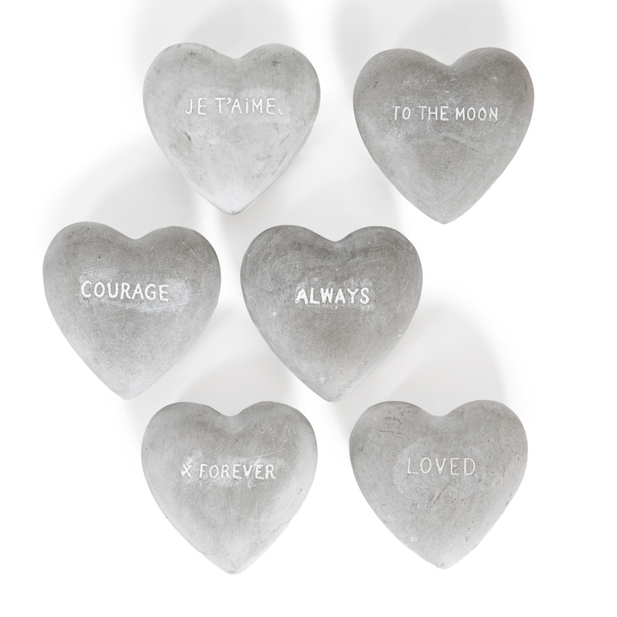 Six heart shaped cement stones with the words: Je T'aime, To the moon, courage, always, X forever, and loved
