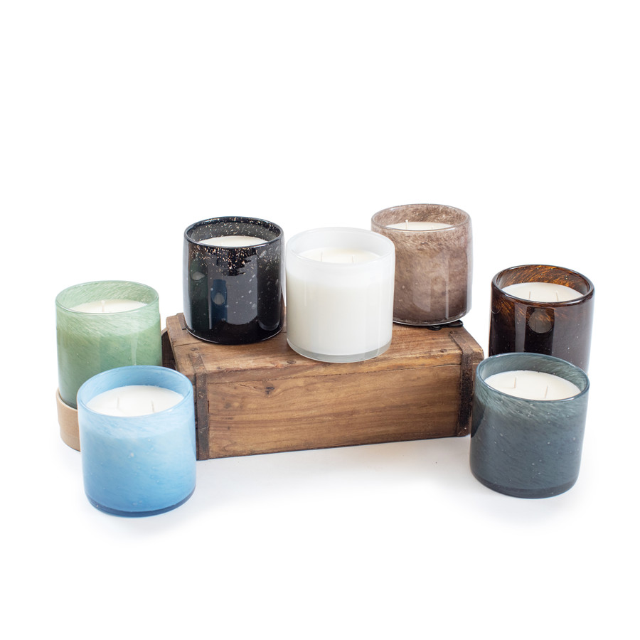 from left to right, a light blue bubble glass candle, and light green bubble glass candle, a charcoal bubble glass candle, a white bubble glass candle, a beige bubble glass candle, a brown bubble glass candle and a turquoise blue bubble glass candle all sitting on a wooden brick mold