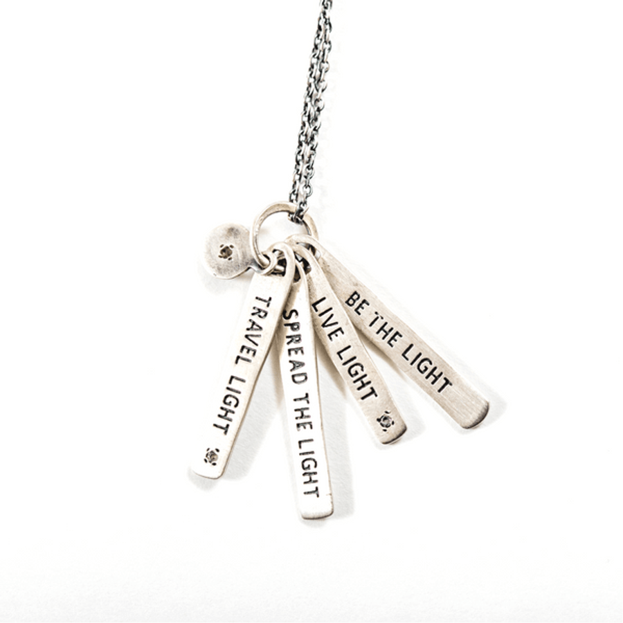 "sterling silver necklace with the quote ""travel light spread the light live light be the light"""