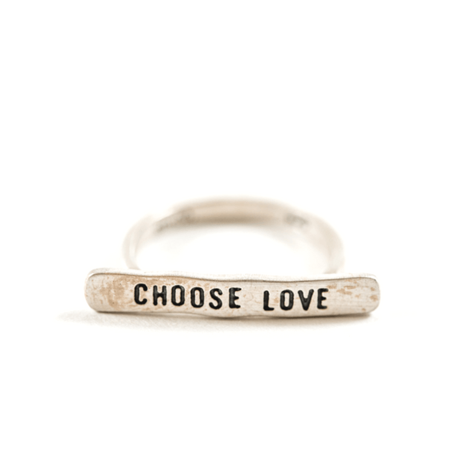 "silver ring with bar that reads ""choose love"""