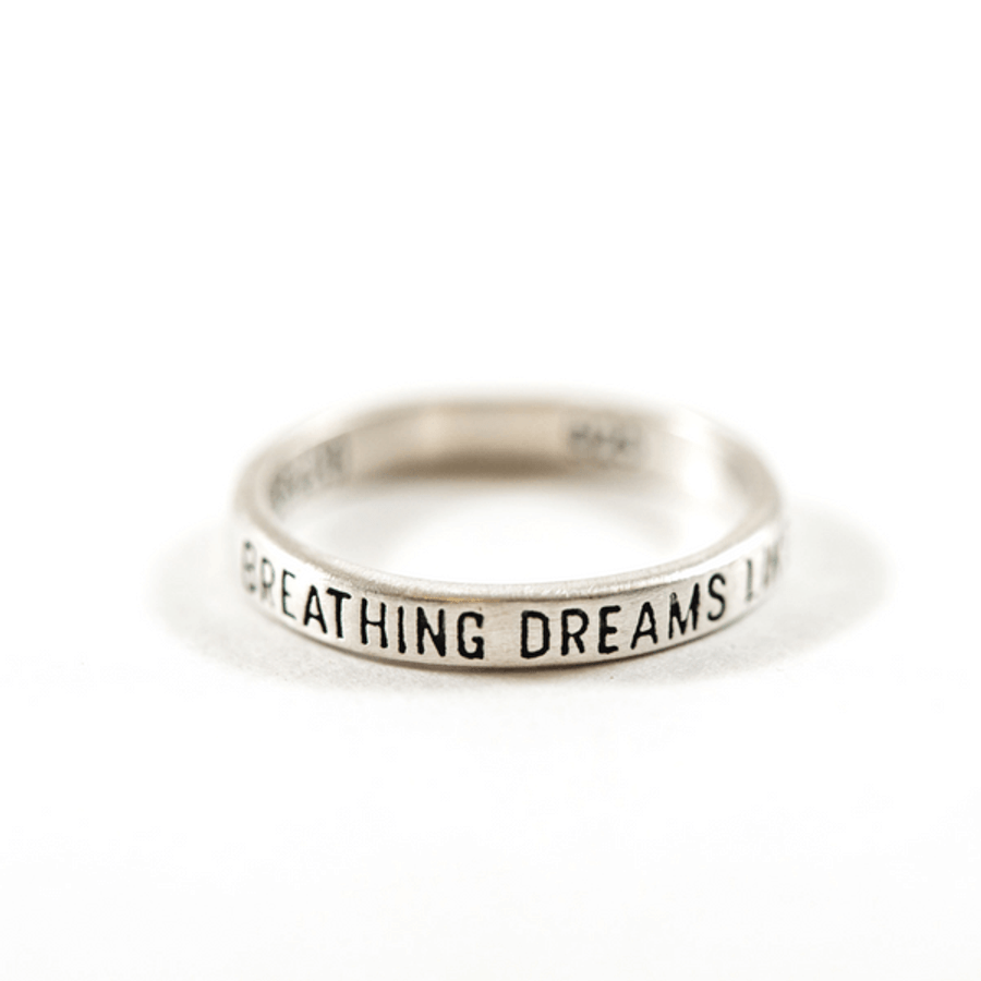 "silver ring with ""breathing dreams like air"" engraved"