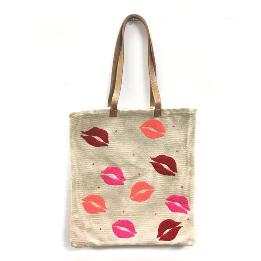 canvas tote bag with leather straps and red and pink lips embroidered